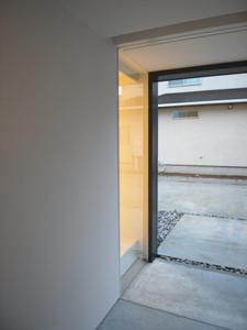 真っ白な玄関土間から外部を見る